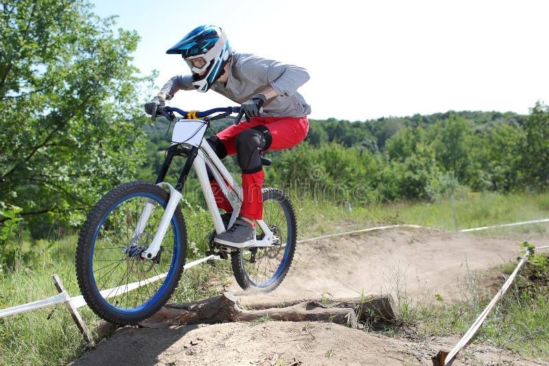 El deportista en ropa de deportes en una bici de montaña monta en el estilo extremo de cuesta abajo imágenes de archivo libres de regalías