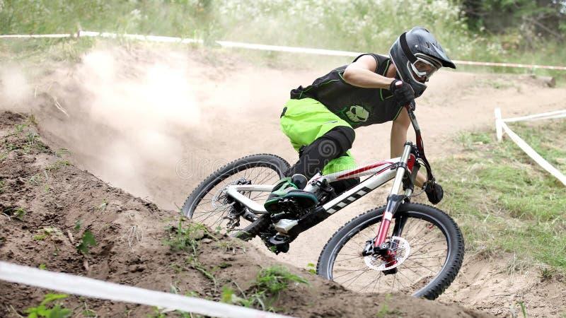 El deportista en ropa de deportes en una bici de montaña monta en las piedras fotos de archivo