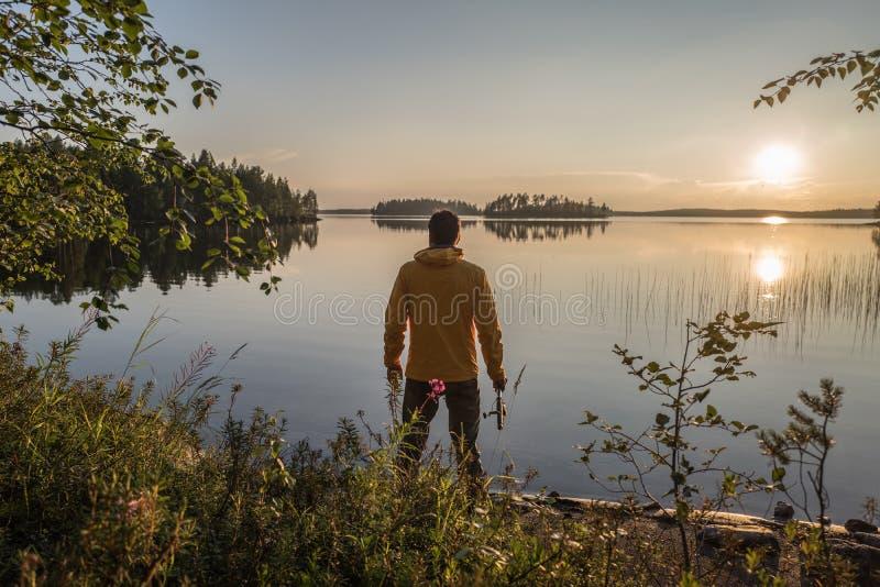 El deportista está pescando en el lago de la puesta del sol fotos de archivo