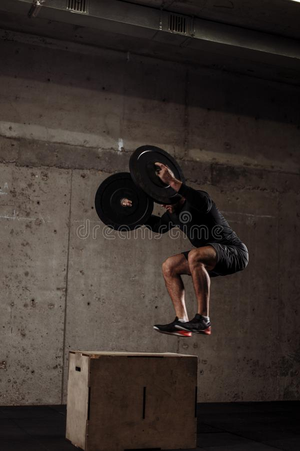 El deportista fuerte que hace el salto se pone en cuclillas con los brazos cruzados en el gimnasio foto de archivo libre de regalías