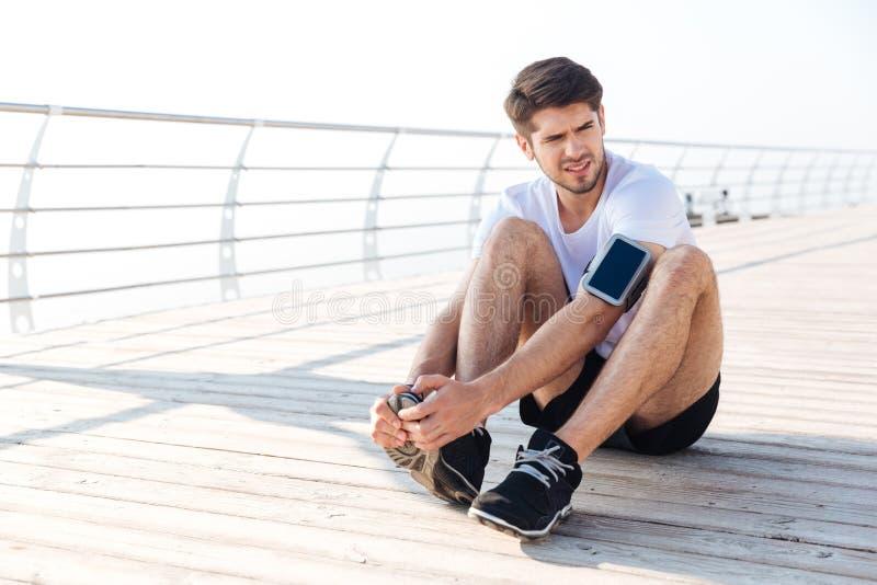 El deportista joven agotado cansó después de correr sentarse al aire libre imagen de archivo