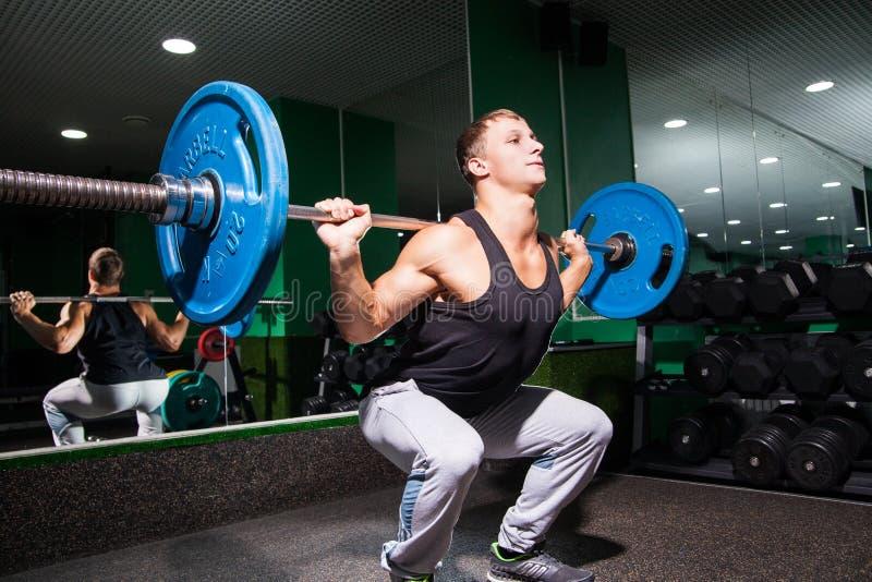 El deportista se pone en cuclillas en gimnasio fotos de archivo libres de regalías