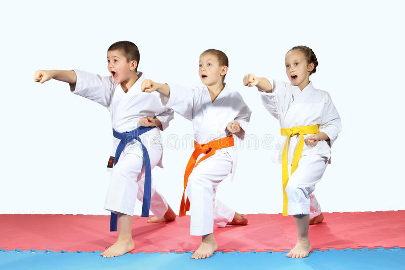 El deportista tres en karategi está golpeando los brazos de los soplos imagenes de archivo