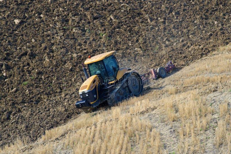 El desafiador catarpillar MT765D en el arado del campo Toscana, Italia fotos de archivo