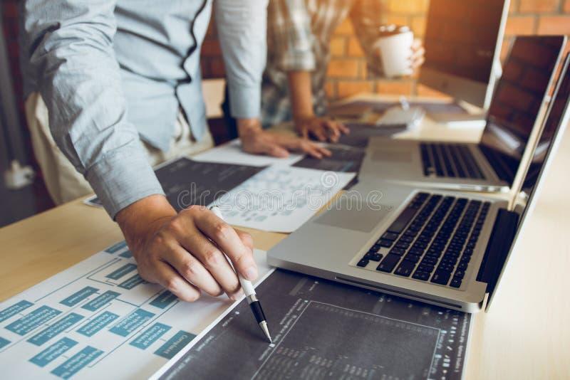 El desarrollador de software está señalando al papel que trabaja y que analiza junto el código escrito en el programa en el orden fotografía de archivo