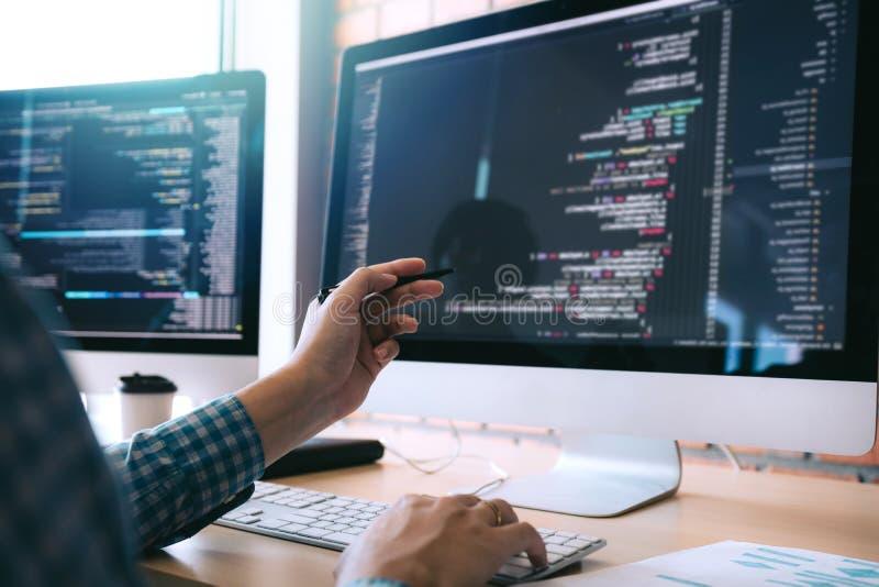El desarrollador de software sostiene la pluma que señala a la pantalla de ordenador y está analizando el código fotos de archivo