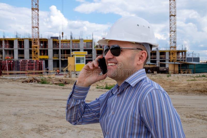 El desarrollador en el casco blanco en el emplazamiento de la obra habla en un teléfono móvil y sonríe imagen de archivo