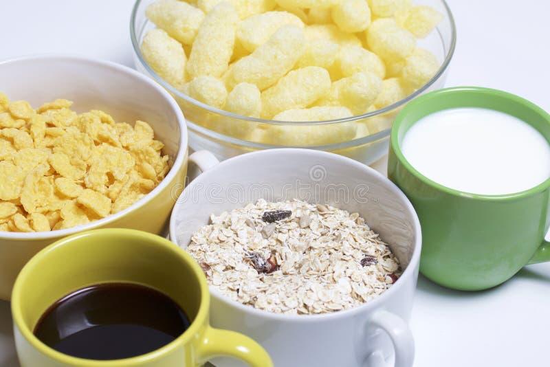 El desayuno útil Muesli, maíz se pega y forma escamas en tazas Allí ` s a la taza de leche y una taza de café En un fondo blanco fotos de archivo libres de regalías