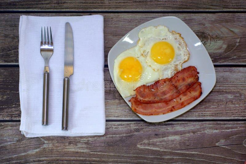 El desayuno caluroso, en la placa los huevos fritos con tocino y un cuchillo con una bifurcación en una servilleta al lado de la  foto de archivo
