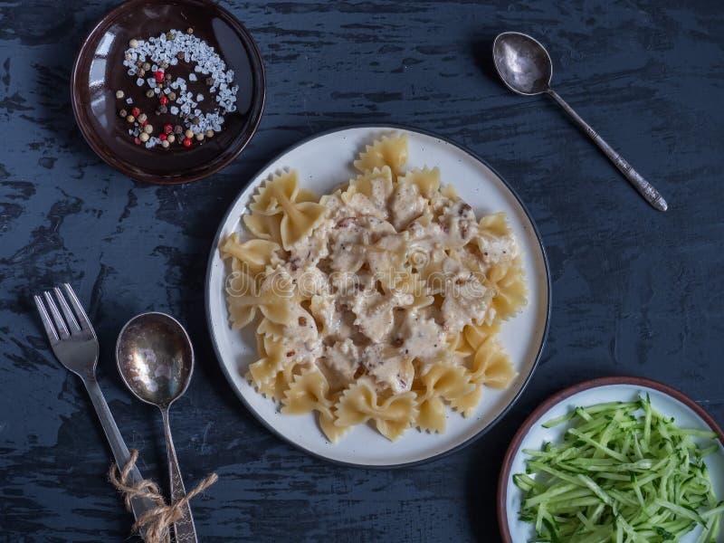 El desayuno de las pastas con la salsa y el ajo cremosos, ralló recientemente la ensalada del pepino en las placas redondas en un imágenes de archivo libres de regalías