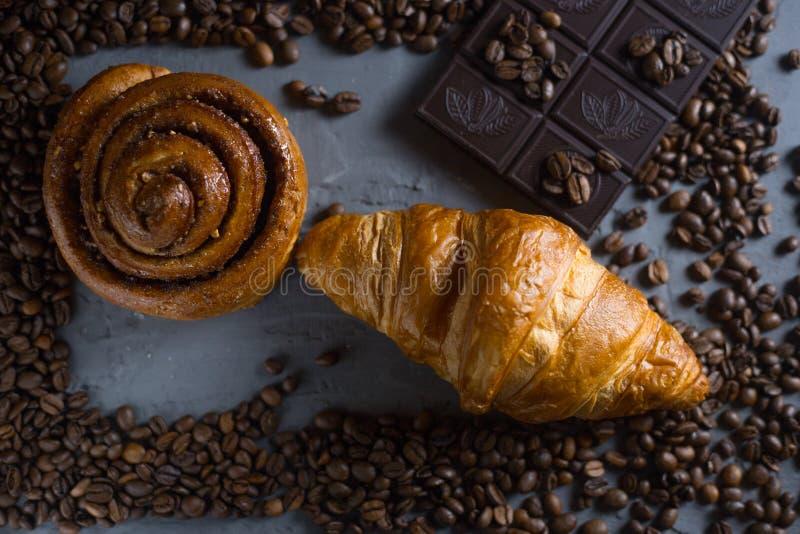 El desayuno del chocolate del cruasán del café arregló en una opinión de top de piedra gris del fondo Foto en un oscuro imagen de archivo libre de regalías