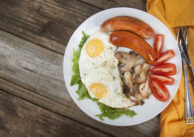 El desayuno inglés Eggs, las salchichas, setas, tomates, pan de la tostada Consumición de la comida tasy sobre la tabla de madera imagen de archivo