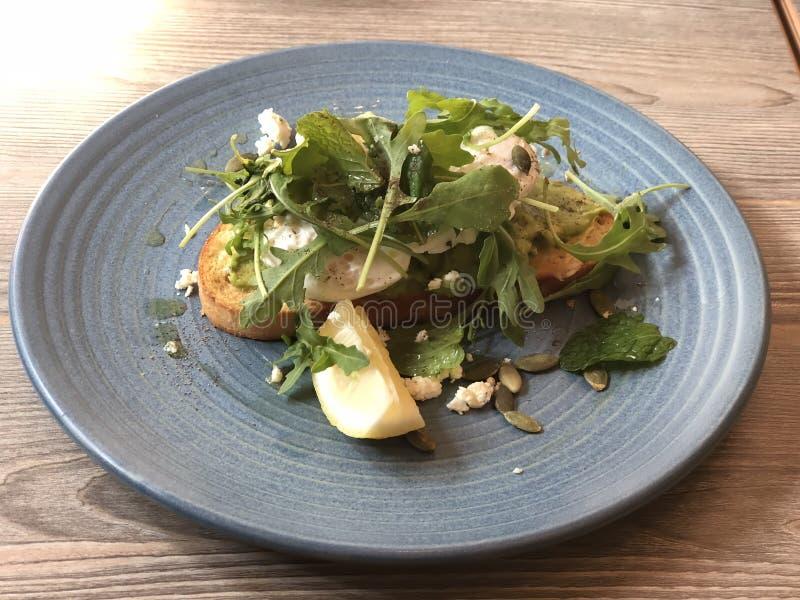 El desayuno ropen el bocadillo rematado con las semillas del limón y de girasol de la rebanada del queso de la ensalada de cohete fotografía de archivo libre de regalías