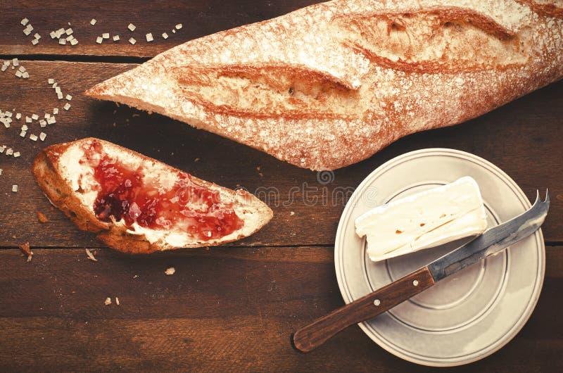 El desayuno sano coció y cortó recientemente el baguette francés con foto de archivo libre de regalías