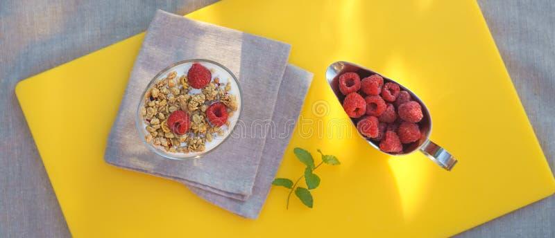 El desayuno sano con el granola hecho en casa de cristal con el yogur y las frambuesas frescas de las bayas en zumo de naranja fr imágenes de archivo libres de regalías