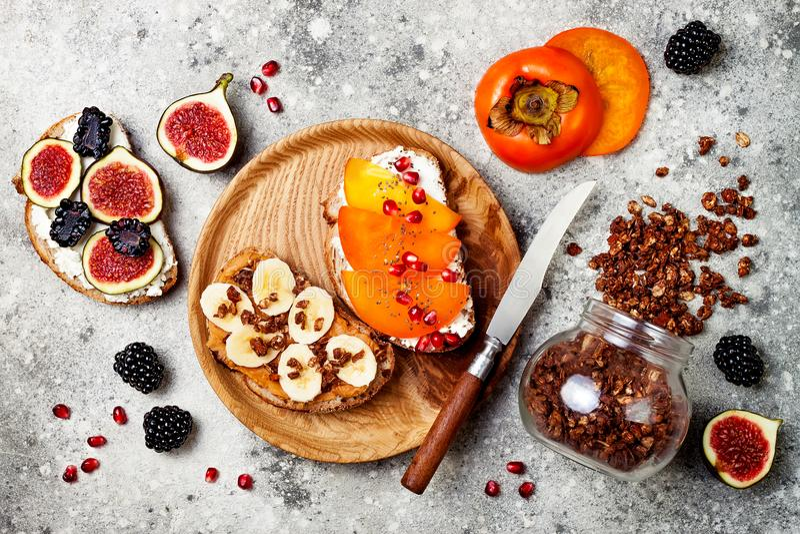 El desayuno sano tuesta con la mantequilla de cacahuete, plátano, granola del chocolate, queso cremoso, higos, zarzamora, caqui,  fotografía de archivo libre de regalías