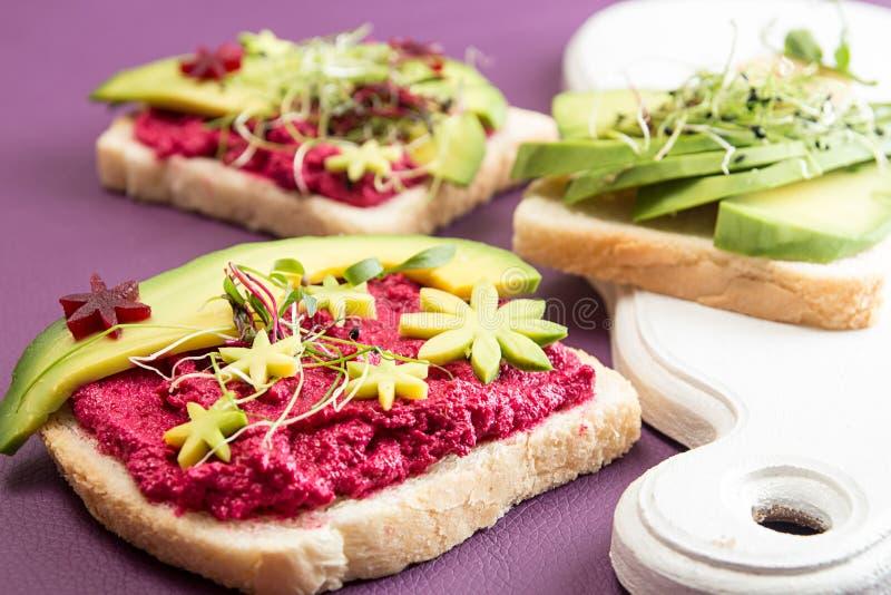 El desayuno sano tuesta con el queso Feta, remolacha, rebanadas de aguacate foto de archivo