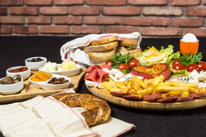 El desayuno turco tradicional con el queso, salami, hirvió el huevo, el tomate, el pepino, las patatas fritas y el pan tostado imagenes de archivo