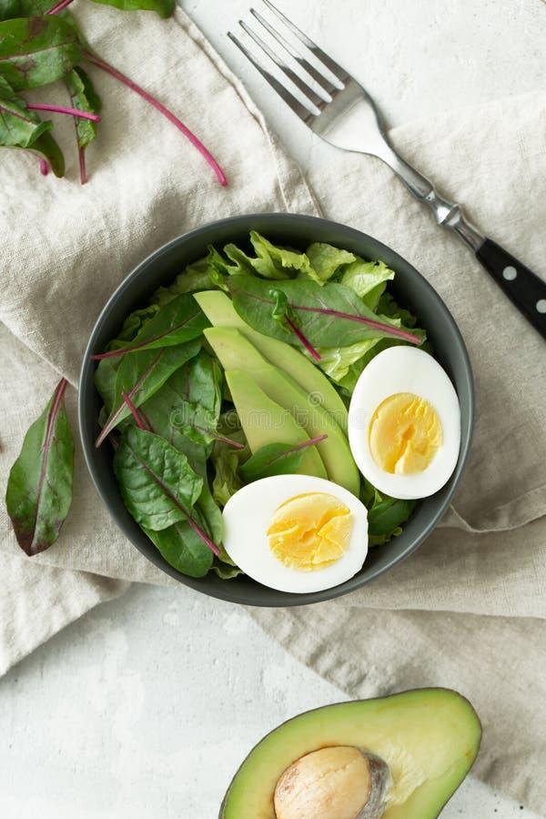 El desayuno vegetariano sano rueda con la ensalada, el aguacate y el huevo, visión superior Consumición limpia, concepto de la co imagenes de archivo