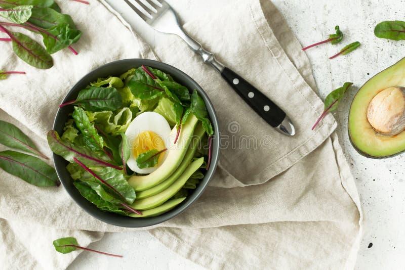 El desayuno vegetariano sano rueda con la ensalada, el aguacate y el huevo, visión superior Consumición limpia, concepto de la co imagen de archivo