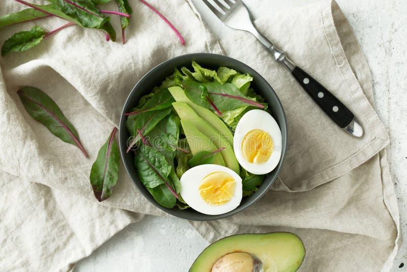 El desayuno vegetariano sano rueda con la ensalada, el aguacate y el huevo, visión superior Consumición limpia, concepto de la co foto de archivo