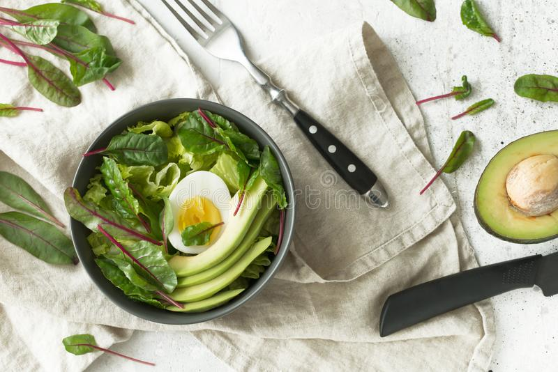 El desayuno vegetariano sano rueda con la ensalada, el aguacate y el huevo, visión superior Consumición limpia, concepto de la co fotos de archivo