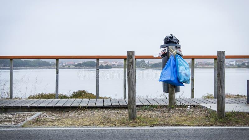 El desbordar trashcan por el agua y al lado de pasarela de madera Prevención contra el plástico en la epidemia del océano fotos de archivo libres de regalías