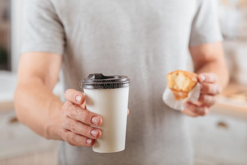 El descanso para tomar caf? se lleva la taza disponible del mollete del hombre foto de archivo libre de regalías