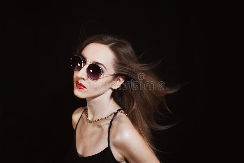 El desgastar de la mujer joven gafas de sol imagenes de archivo