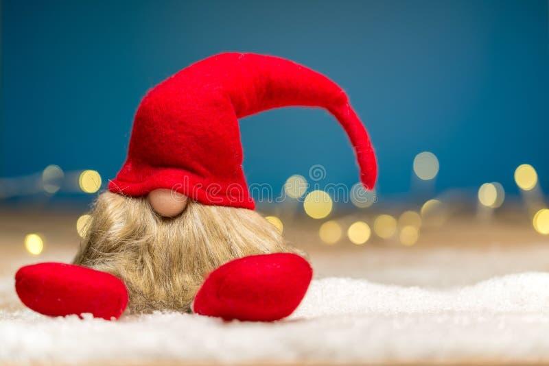 El desgraciado rojo de la Navidad que se sienta en nieve delante del bokeh enciende foto de archivo