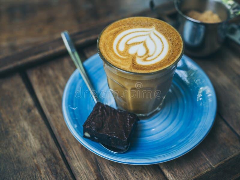 El desmoche de flautín del café del Latte con arte de la flor de la leche en pequeño vidrio con un pedazo de brownie hechos en ca imagen de archivo libre de regalías