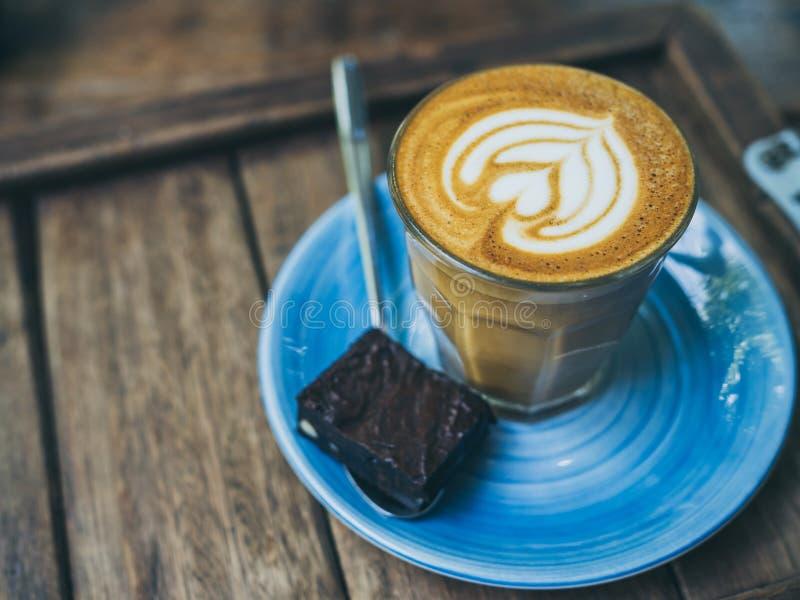 El desmoche de flautín del café del Latte con arte de la flor de la leche en pequeño vidrio con un pedazo de brownie hechos en ca imagenes de archivo
