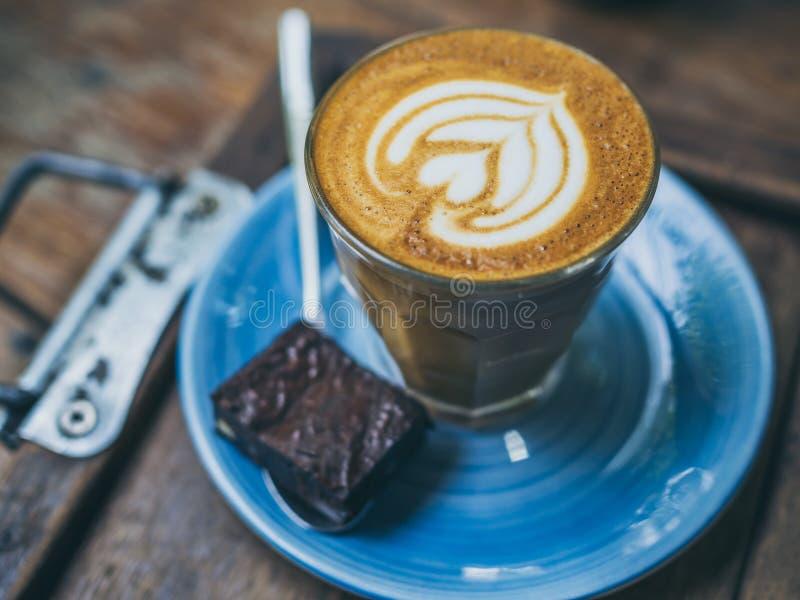 El desmoche de flautín del café del Latte con arte de la flor de la leche en pequeño vidrio con un pedazo de brownie hechos en ca imagen de archivo