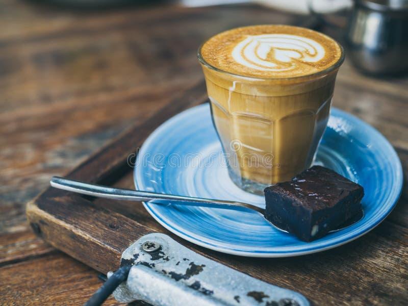 El desmoche de flautín del café del Latte con arte de la flor de la leche en pequeño vidrio con un pedazo de brownie hechos en ca fotos de archivo libres de regalías
