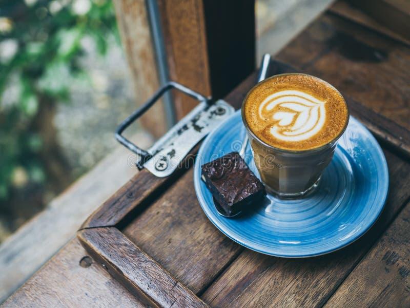 El desmoche de flautín del café del Latte con arte de la flor de la leche en pequeño vidrio con un pedazo de brownie hechos en ca foto de archivo libre de regalías