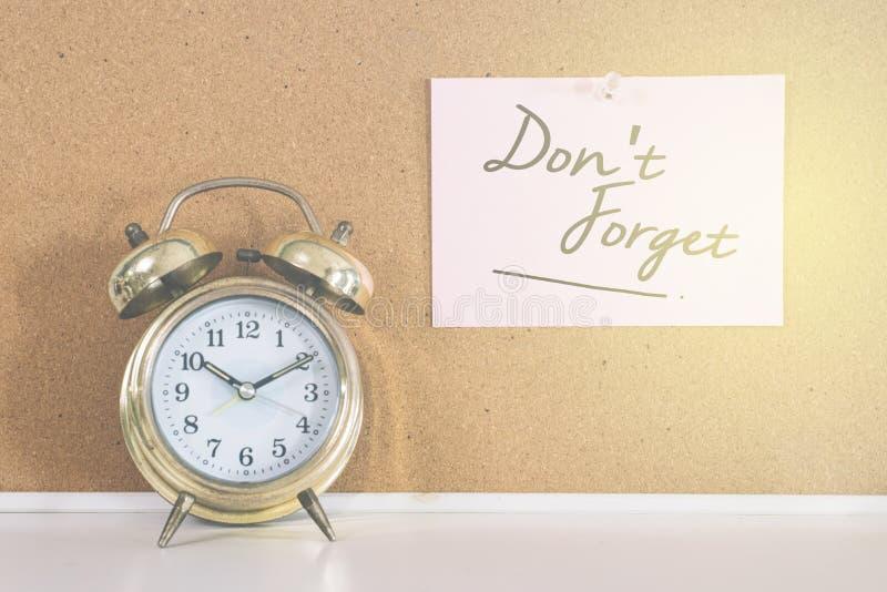El despertador de la campana de oro y una nota escrita el ` T de DON OLVIDAN en un tablero del corcho imagen de archivo