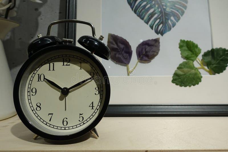 El despertador del primer para adorna alrededor de las cosas para el diseño de la decoración interior en el escritorio de madera  foto de archivo libre de regalías