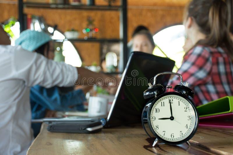 El despertador en la tabla de madera con el fondo abstracto borroso de la gente de la discusión del negocio agrupa o del equipo d imagen de archivo libre de regalías