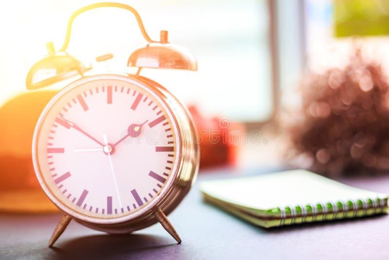 El despertador está en la tierra Un papel, un sombrero y una flor cerca del reloj fotografía de archivo