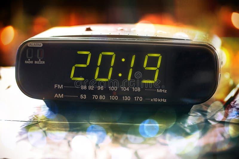 El despertador está mostrando medianoche Es veinte diecinueve, Navidades y bokeh, Feliz Año Nuevo del día de fiesta fotos de archivo