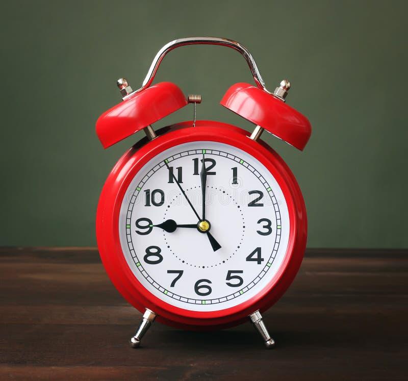El despertador rojo que muestra 9-00 horas fotografía de archivo libre de regalías