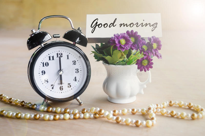 El despertador y la buena mañana marcan con etiqueta con la flor violeta fotos de archivo