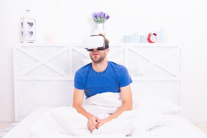 El despertar consciente. Volver a la realidad. El hombre explora el vr mientras se relaja en la cama. Tecnología VR y futuro. Com imagen de archivo