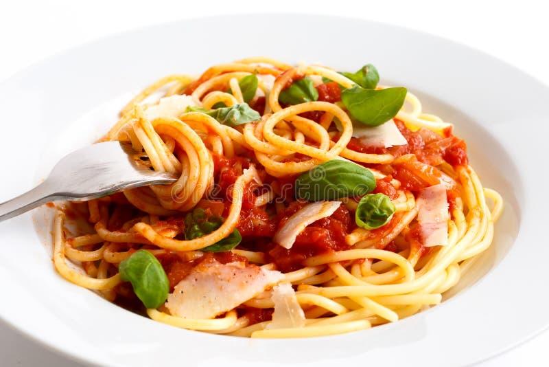 El detalle de espaguetis rodó sobre la bifurcación, la salsa de tomate, la albahaca y el ch fotos de archivo