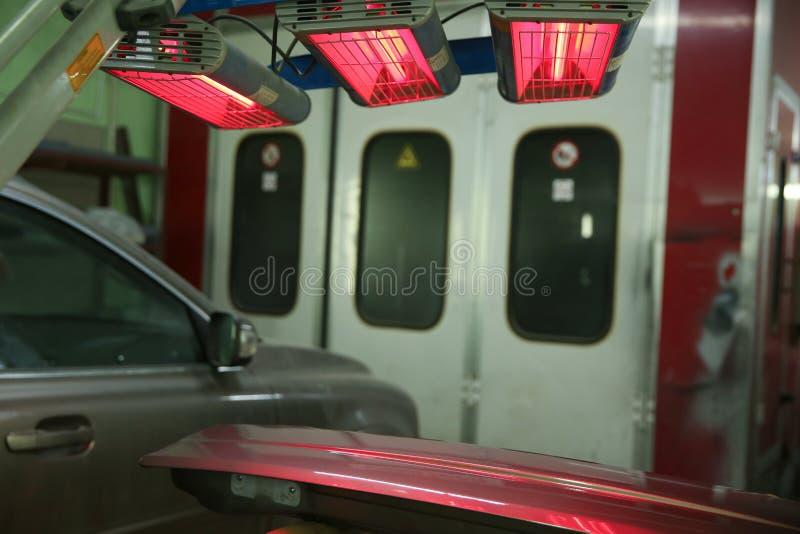 El detalle de la carrocería se está secando debajo de las lámparas después de pintar fotos de archivo libres de regalías