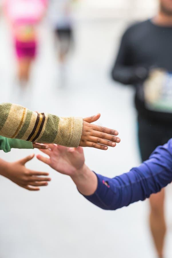 El detalle de los niños que hacen altos fives y motiva los corredores imágenes de archivo libres de regalías