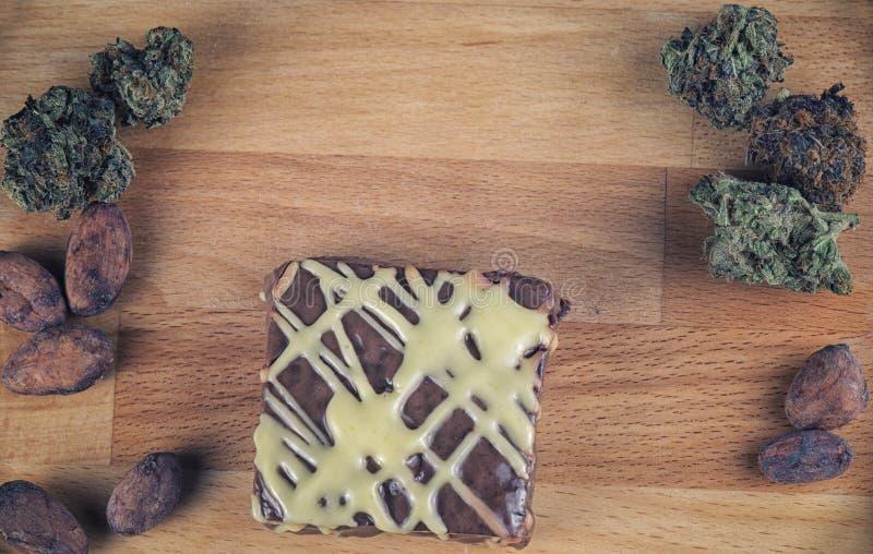 El detalle del brownie del pote sobre la madera con el cáñamo florece imagen de archivo