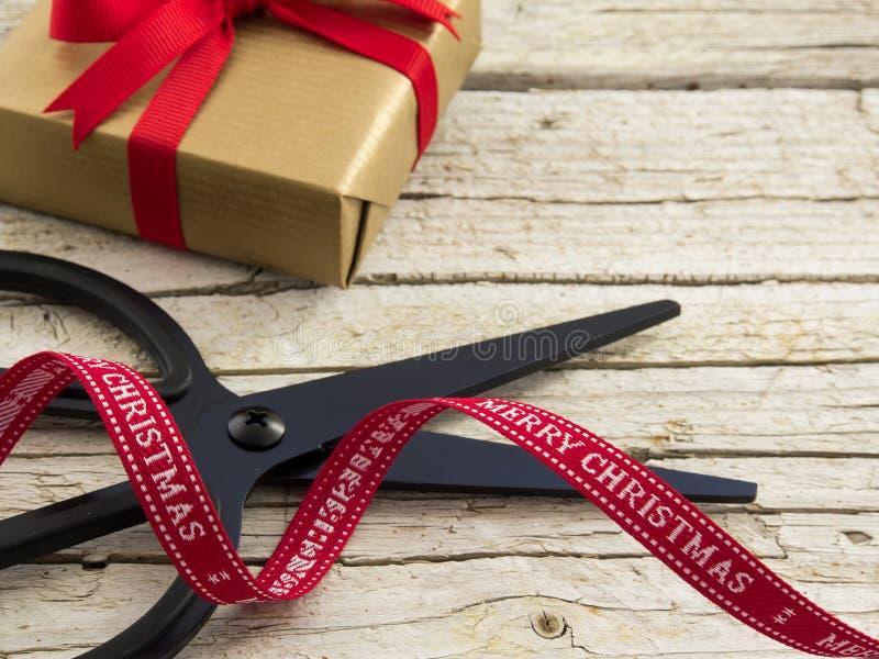 El detalle del negro retro scissor, regalo y cinta roja en el CCB de madera imagen de archivo