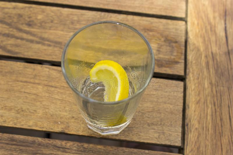 El detalle del primer tiró del limón fresco en vidrio vacío en la mesa de desayuno mediterrian en Grecia, isla de Lesvos imagenes de archivo