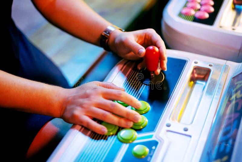 El detalle en las manos que sostienen la palanca de mando y que empujan abotona en un cuarto del juego fotos de archivo